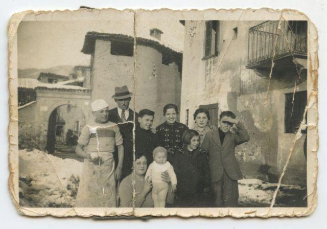 Cadestore, frazione di Villa d'Adda, 1938 – Il bambino sulla sinistra con una pagnotta in mano è Carlo, scomparso in Russia nel 1943. Alla destra di Giuseppe (il terzo da sinistra) c'è il padre Camillo. Alla sua sinistra la sorelle Teresa, Adele e Anita e il fratello Rizieri. La famiglia viveva nella casa di cui si scorge una parete sulla destra